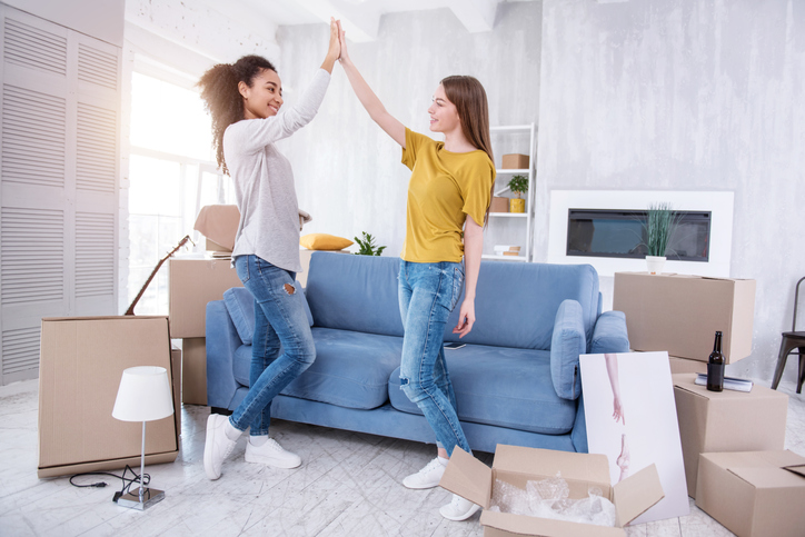 Two students high fiving in an unpacked apartment.