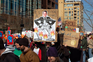 More protesters. The sign centred in the photograph is a picture of a man's head attached to a cartoon body with its pants on fire. These are on a cardboard backing, which has the caption 'It's A Fiscal Issue!'