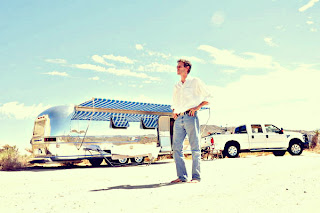 Josh Needleman stands in front of the Peacock Alley Airstream trailer