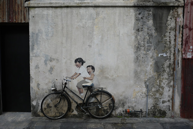 real bicycle against a wall with painted bicycle riders in George Town, Penang, Malaysia