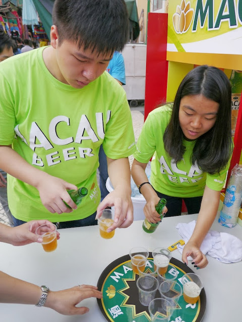 two people pouring samples of Macau Beer