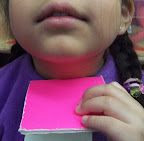 Pink light is reflected from smooth pink cardboard onto a child's skin.