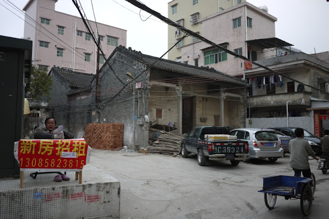 many sitting behind a sign near some older buildings in Nanping, Zhuhai