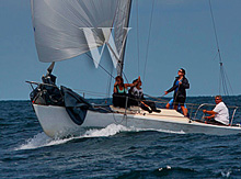 J/24 one-design sailboat- sailing fast down surfing wave