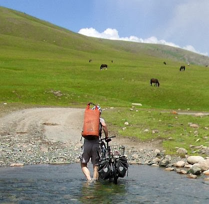 Waten mit Fahrrad ohne Schuhe durch einen kleinen Nebenfluss des Solton-Sary, Kirgistan