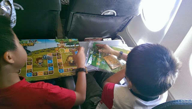 The boys playing a board game on the plane