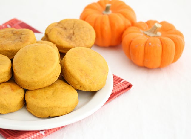 photo of biscuits on a plate with two small pumpkins in the background