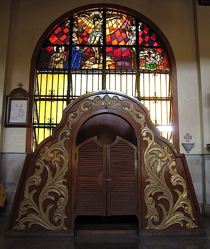 a stained glass window and confessional at the Agoo Basilica