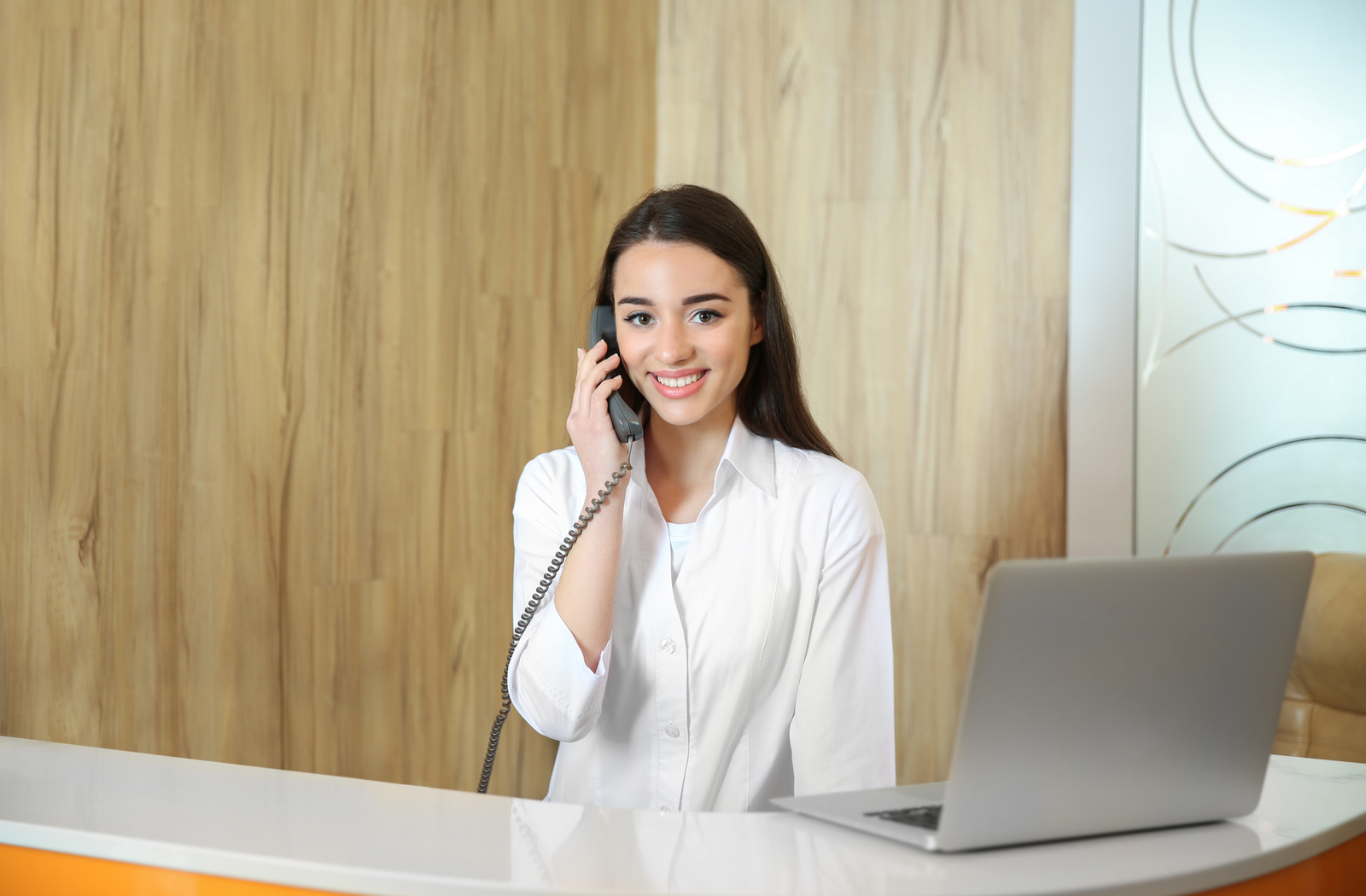 dental receptionist with dark hair smiling on the phone while she calls due patients
