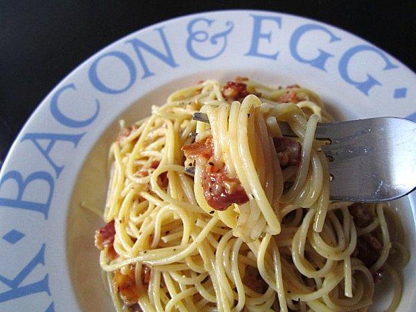 a fork twirling spaghetti alla carbonara around it