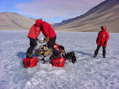 Jill Mikucki and Craig Wolf drill a sampling hole on Lake Vanda, 2002