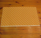 Lay the once-folded fabric down on a flat surface, such as a clean floor.