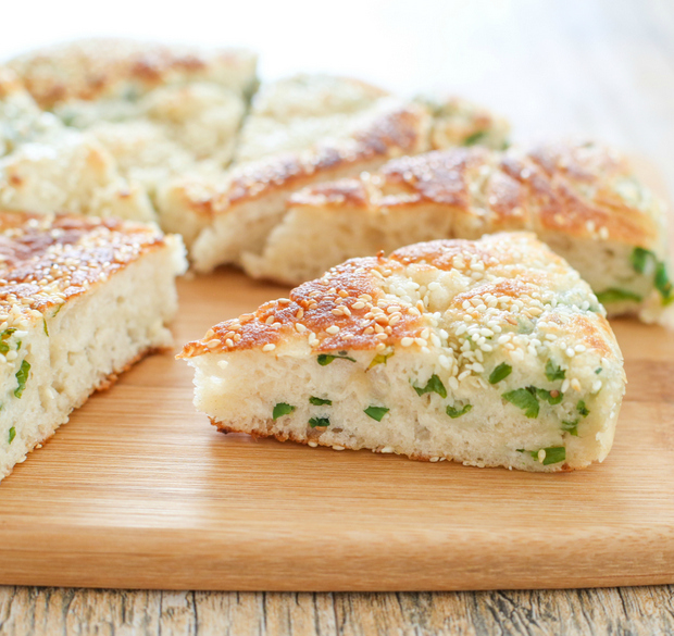 a slice of Chinese sesame scallion bread on a cutting board