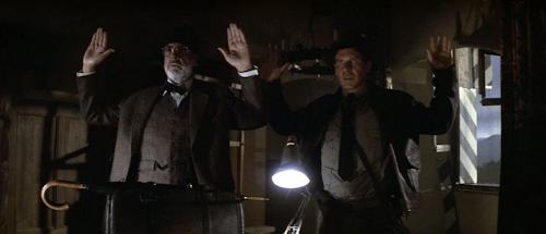 Henry and Indiana Jones at gunpoint.