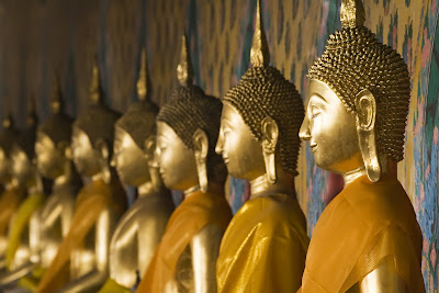 Row of seated Buddhas at the temple of Wat Arun in Bangkok, Thailand.