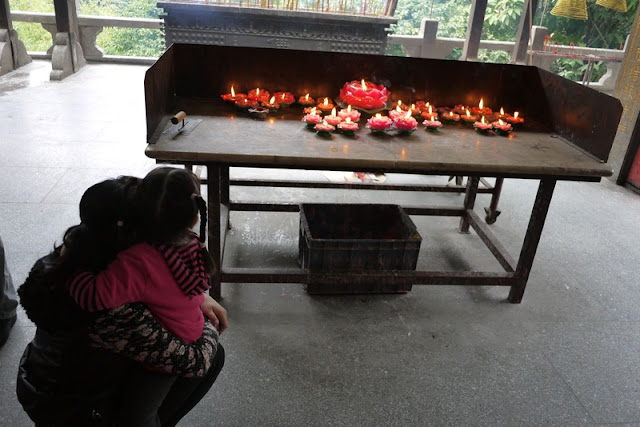Mother and daughter looking at lotus flower shaped candles at Bailian Dong park in Zhuhai China