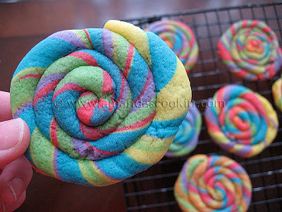 A close up photo of a St. Patrick\'s day rainbow cookie with more in the background.