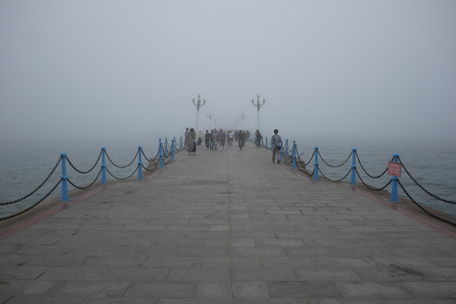 a pier disappearing into the fog