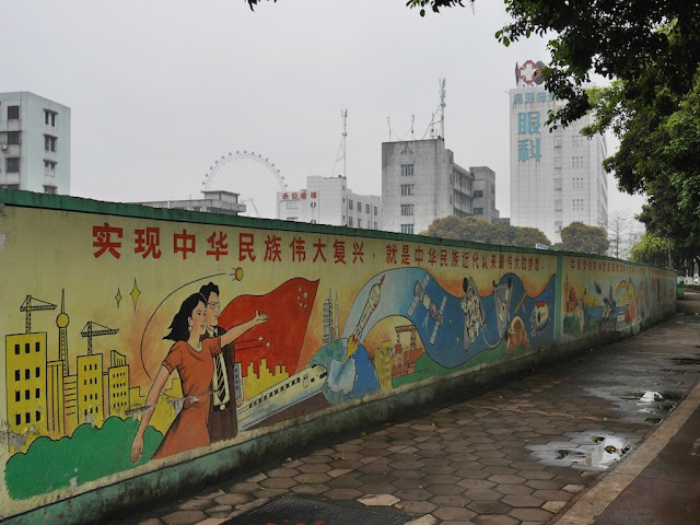 "patriotic mural depicting some of China's recent achievements with the Chinese ""实现中华民族伟大复兴,就是中华民族近代来最伟大的梦想。"""