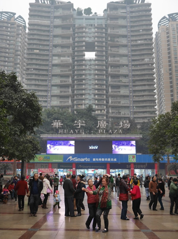 A group of people dance in a large square in Shapingba, Chongqing.