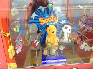 Sooty, Sweep and Soo playing music in an amusement arcade by the beach