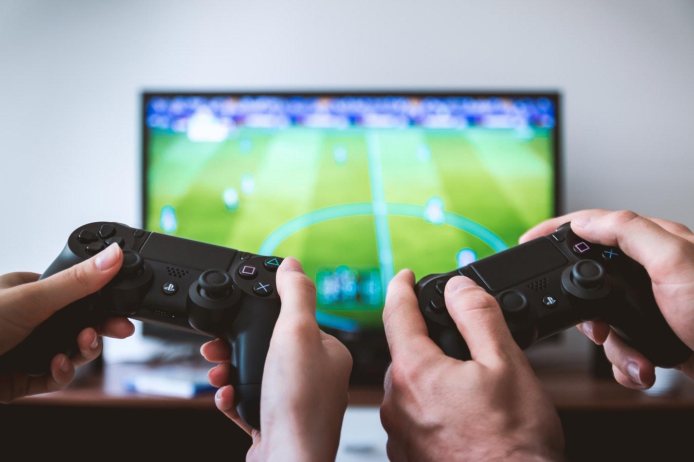 兩雙手一起握著遊戲握柄,面對足球賽電玩的螢幕。