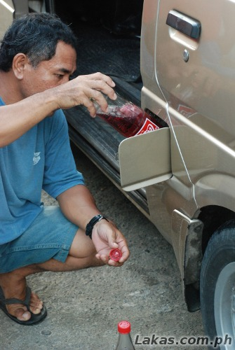 Red Coke being poured into a vehicle