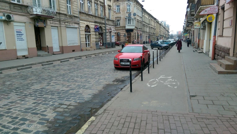 Jednokierunkowa ulica z drogą dla rowerów (jdnokierunkową) po jednej stronie i separowanym pasem po drugiej