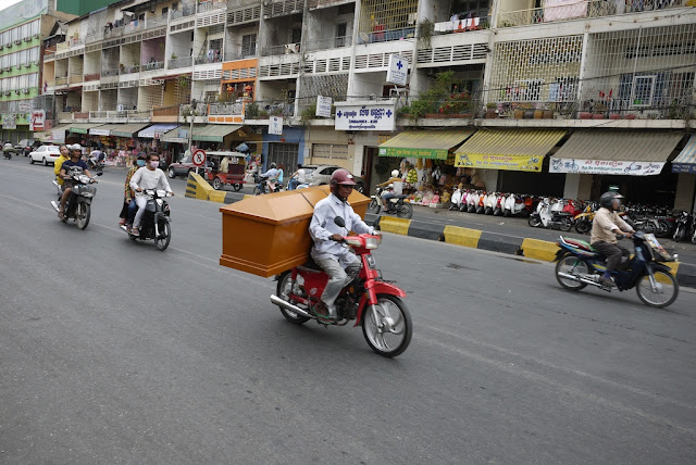 man carrying a coffin on a motorbike
