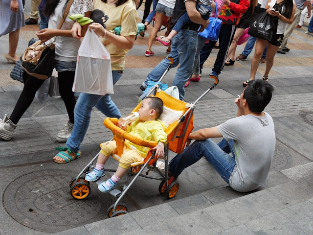 man sitting down and smoking next to a child in a stroller