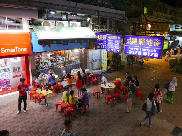 people eating outside on a pedestrian street in Tsuen Wan, Hong Kong