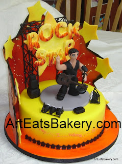 Yellow and orange airbrushed Rockstar birthday cake with sugar figure, guitar, microphone, speakers, lights and stage