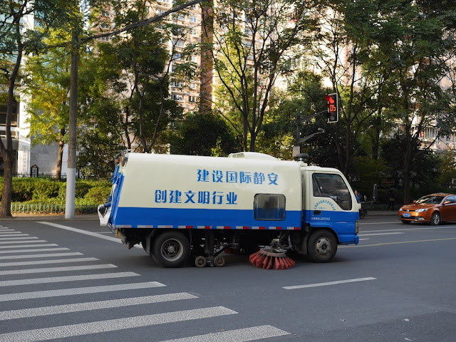 "road sweeper truck with the slogan ""建设国际静安 创建文明行业"" on it cleaning a street in Shanghai"