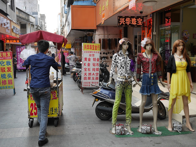 man pushing a food stall past mannequins in Yangjiang, China