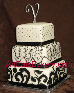 Black and off white three tier square fondant cake with hand piping and painting.