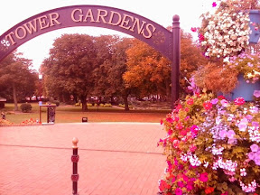 A flowery Tower Gardens arch entrance at Skegness showing trees going into autumnal color