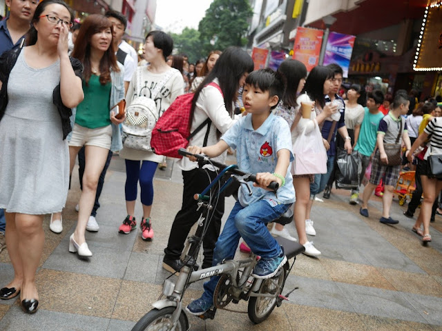 boy riding a bike on a pedestrian street in Dongmen