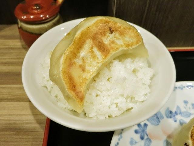 ご飯に乗せた餃子。大きめの丼の径と同じぐらいの大きさ。。