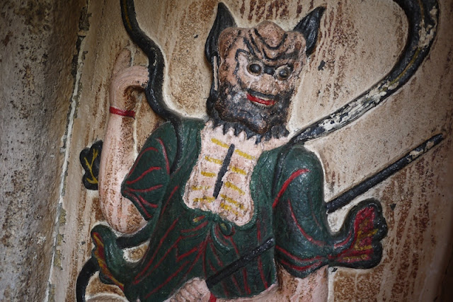 carved and painted figure on a wall at A-Ma Temple in Macau