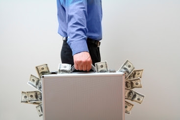 man carrying a suitcase with money spilling out