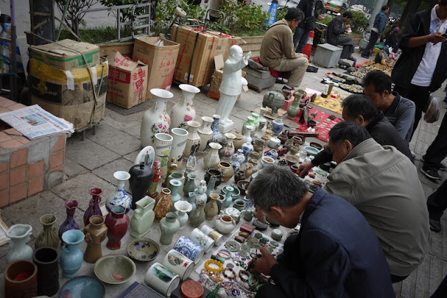 people examing items on the ground for sale outside Tianxinge Antique City in Changsha, China
