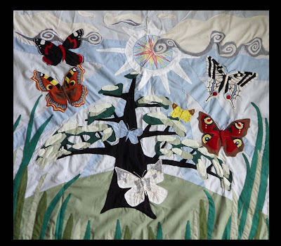 Machine appliqué with butterflies and tree. Foreground is long grass and background with large sunshine and clouds