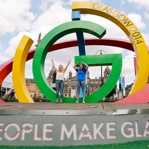 Alicia Steer (L) and Gemma MacLean pose on 'The Big G' 3-D structure at George Square in Glasgow, Scotland, July 22, 2014. The opening ceremony of the Glasgow 2014 Commonwealth Games takes place on July 23.