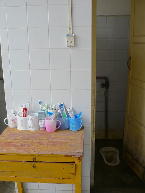 bathroom with squat toilet in dorm room at the Guangxi Normal University for Nationalities in Longzhou, China