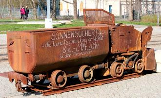 Bergwerkslore mit Aufschrift: »Sonnensucher! Die Kunstsammlung der Wismut. 8.2. bis 21.4.2014«.