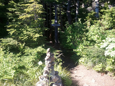 A cairn and sign mark the correct trail branch to follow