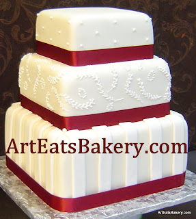Three tier square fondant wedding cake with red ribbons, dots, stripes and leaf pattern  royal icing picture