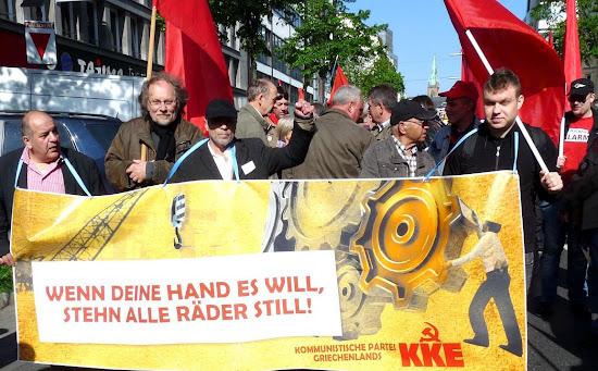 Demonstranten mit Transparent: »Wenn deine Hand es will, stehn alle Räder still!  KKE«.