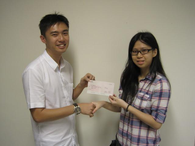 Koh Mingxuan's sister (right) receiving the Bursary Award from Mr Lim Kian Kiat, Treasurer of AJCAA.