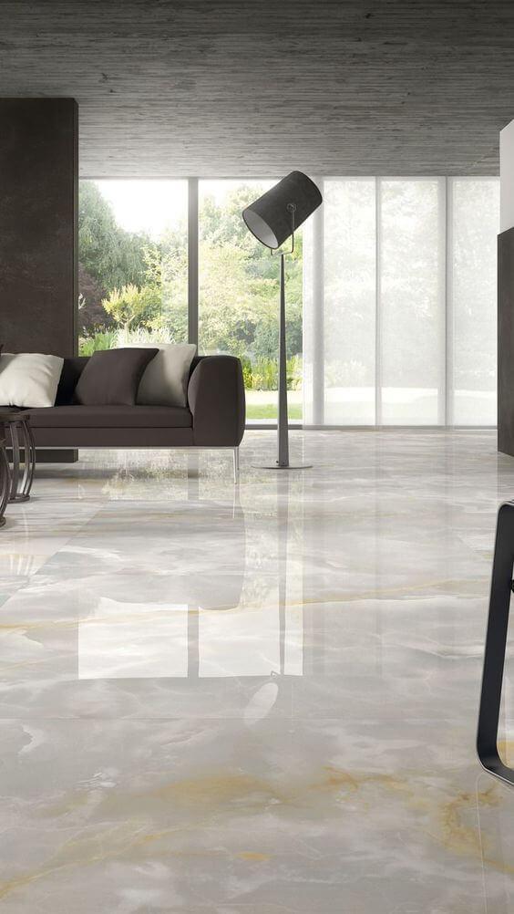 Sala de estar com porcelanato imitando mármore em tons claros, sofá chumbo, luminária chumbo de chão e porta envidraçada com cortina longa branca